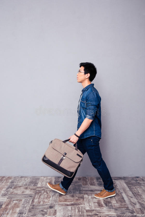 Man walking in jeans wear and bag royalty free stock images