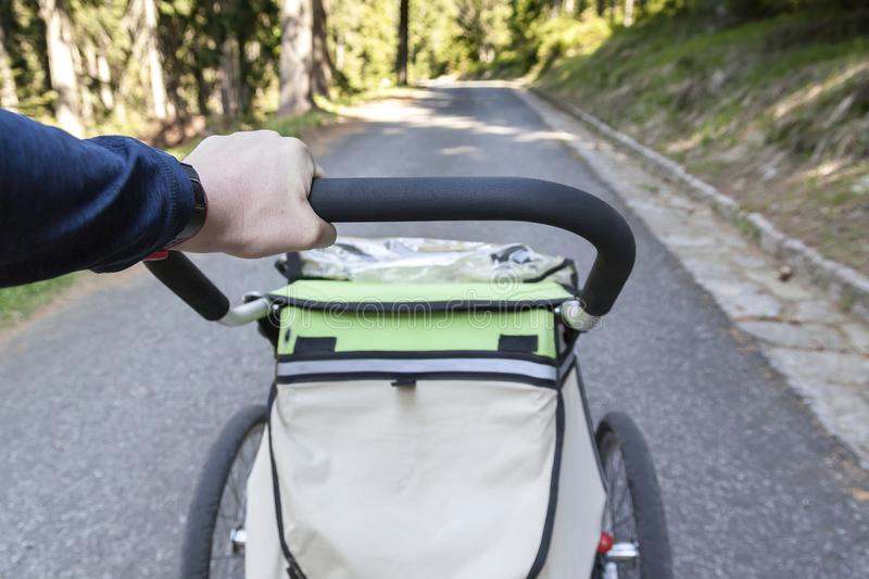 Man walking and jogging outdoors with child jogging stroller royalty free stock photo