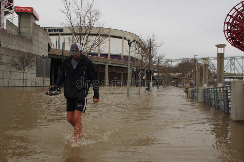 Man walking through Ohio River flood 2018. A man walks through flooded Ohio River along the Cincinnati waterfront on Feb. 25, 2018, when the river hit 60 foot royalty free stock photos