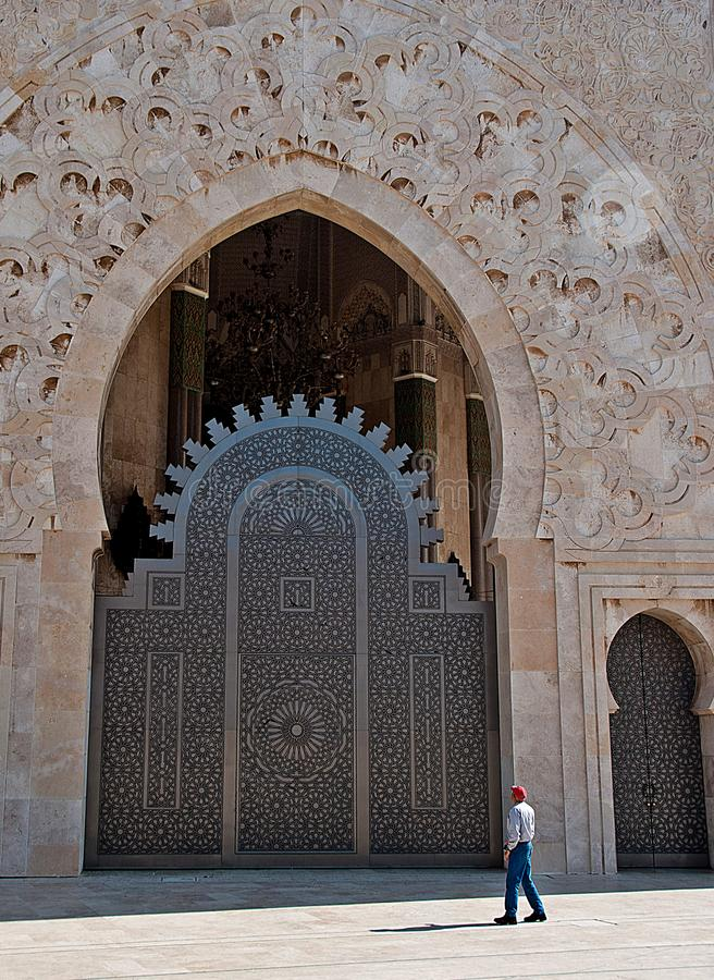 Man walking through one of the doors of the mosque in Casablanca royalty free stock photos