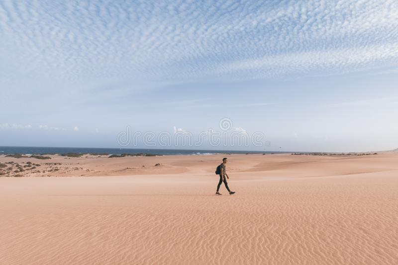 Man walking outdoors in Fuerteventura, Spain. A young caucasian man, carrying a backpack, walking by the Corralejo dunes in Fuerteventura, Canary Islands, Spain stock photos