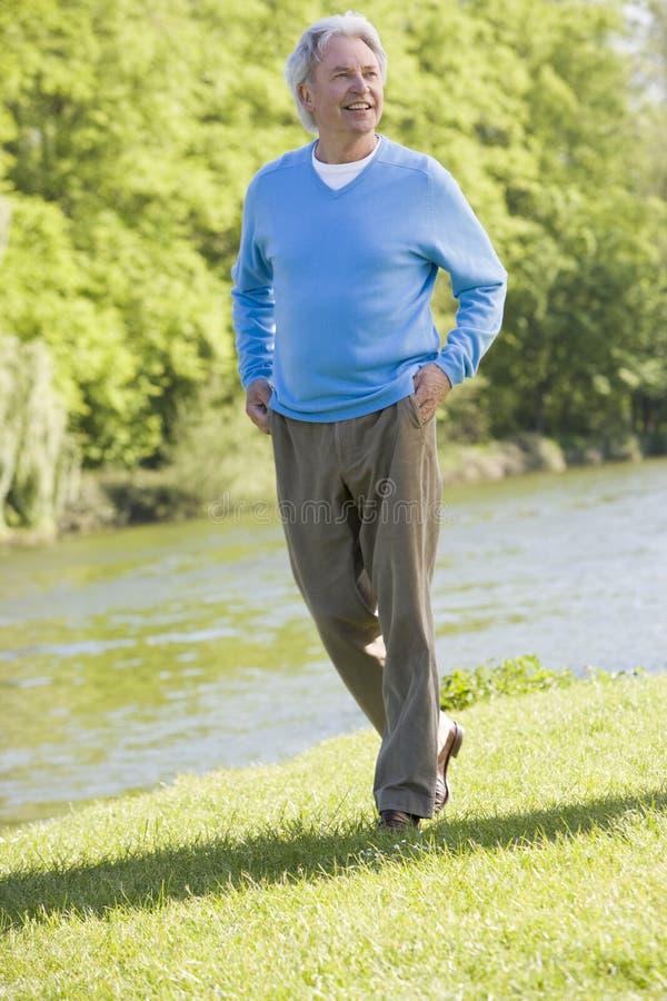 Man walking outdoors at park by lake smiling stock images