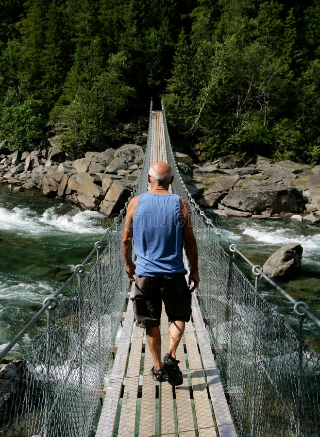 Man walking over a suspension bridge royalty free stock photo