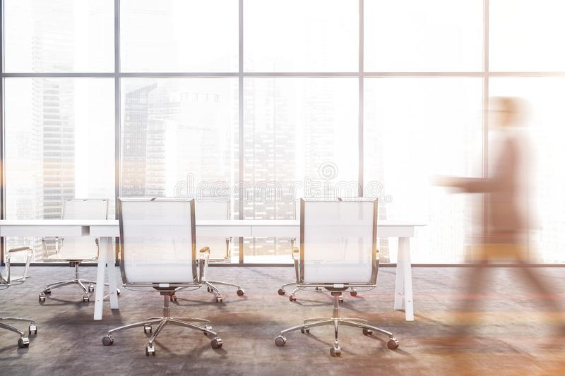 Man walking in panoramic meeting room. Blurry young businessman walking in panoramic conference with long white table with chairs. Concept of negotiations. Toned stock photo