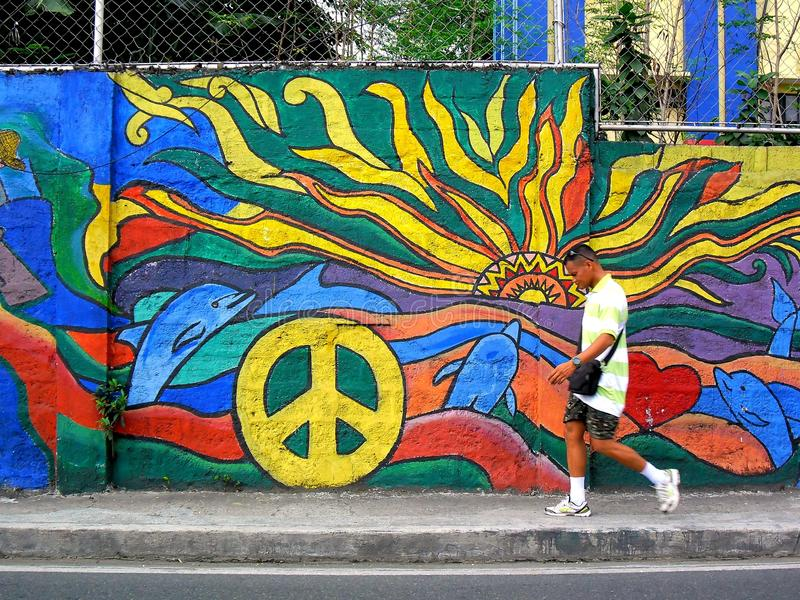 A man walking past a street wall art. Photo of A man walking past a street wall art in quezon city, philippines in asia stock photography