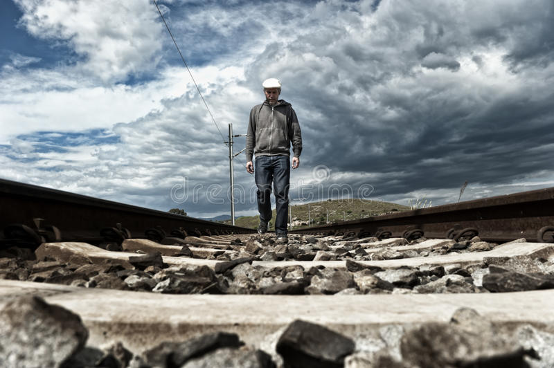 Man walking on the railway tracks. In a desert area royalty free stock photos