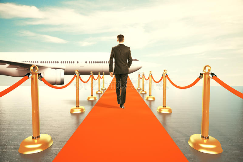 Man walking on red carpet to the first class of plane. Businessman walking on red carpet to the first class of plane stock photos