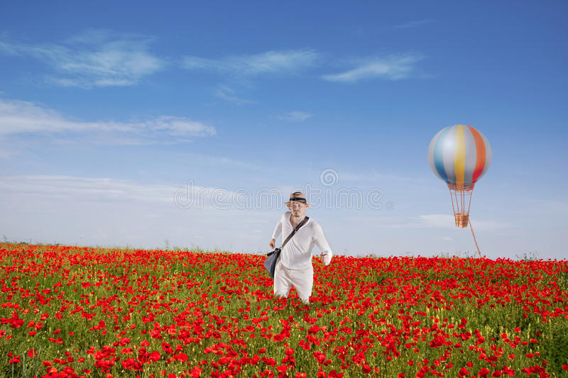 Man Is Walking Through Red Poppy Field Stock Photo