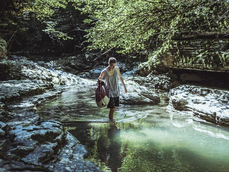Man Walking on River in Between Stone and Tree royalty free stock photos