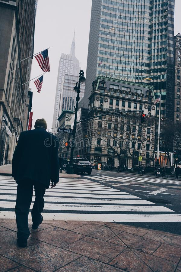 Man Walking on Road Wearing Suit Jacket and Dress Pants Beside High-rise Concrete Buildings royalty free stock photos