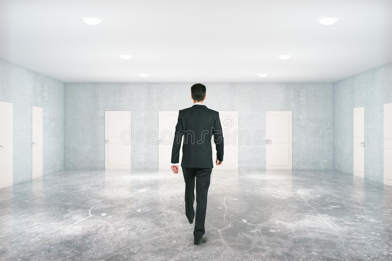 Man walking in room with doors royalty free stock image