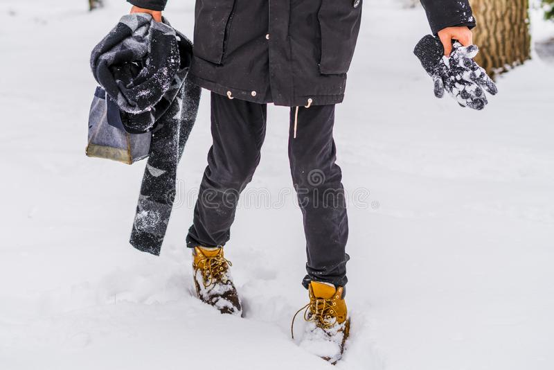 Man walking in snowy weather wearing boots and warm clothes b. Man walking in snowy weather wearing boots and warm clothes royalty free stock photo