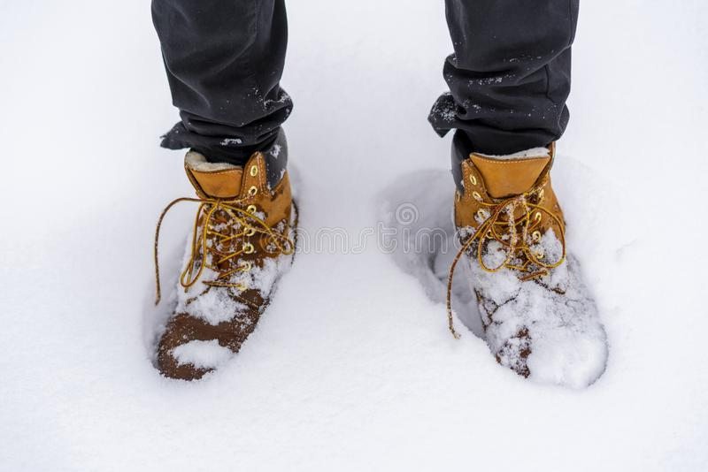 Man walking in snowy weather wearing boots and warm clothes b. Man walking in snowy weather wearing boots and warm clothes royalty free stock photos