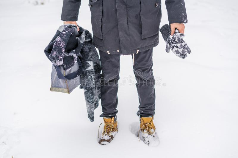 Man walking in snowy weather wearing boots and warm clothes b. Man walking in snowy weather wearing boots and warm clothes stock photo