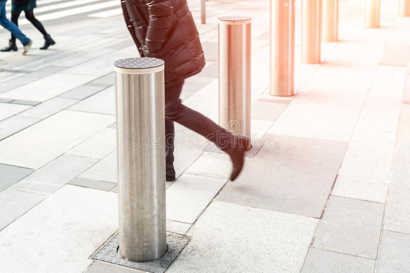 Man walking by stainless steel bollard entering pedestrian area on Vienna city street. Car and vehicle traffic access control stock photo