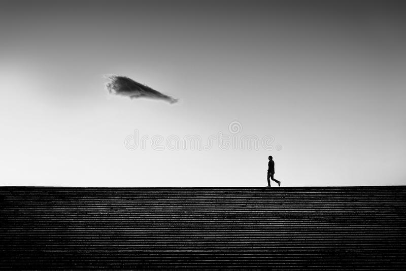Man walking on a staircase with solitary cloud royalty free stock photo