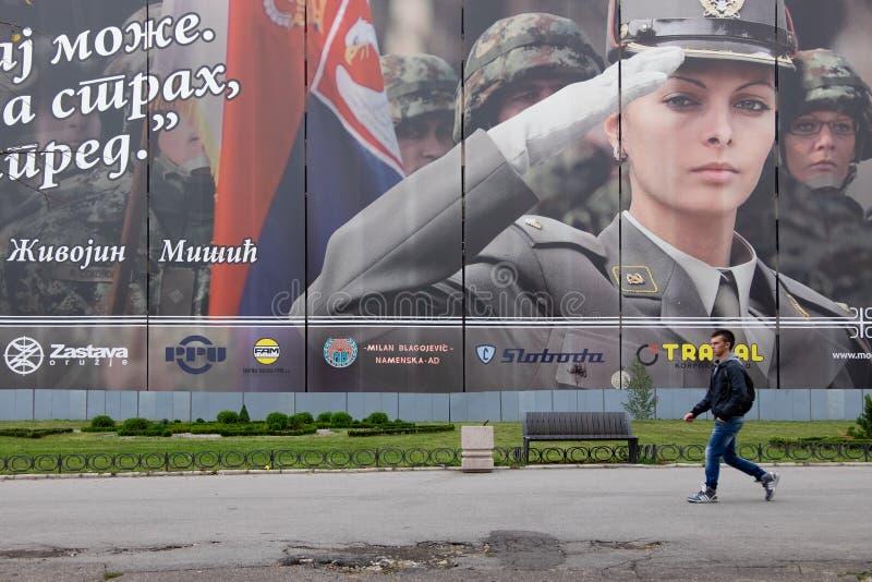Man Walking in the Street. Belgrade, Serbia - September 07, 2016: Unknown man walking in front of a military propaganda in Belgrade stock images