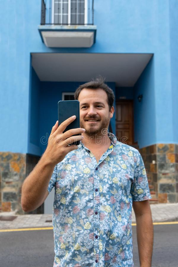 Man walking in the street with his smart phone, making a plan with his college and smiling. Caucasian hipster with beard out of. His blue house. record a video stock image