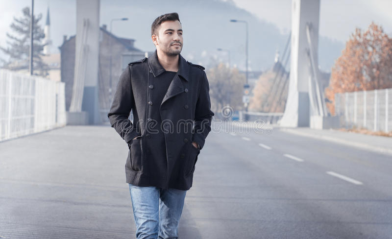 Man walking on street. Young man walking on street, autumn or winter cold day. Outdoors, outside. Gorgeous guy in coat royalty free stock images
