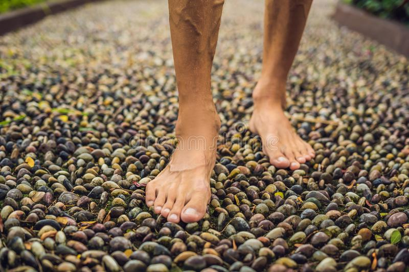 Man Walking On A Textured Cobble Pavement, Reflexology. Pebble s. Tones on the pavement for foot reflexology stock image