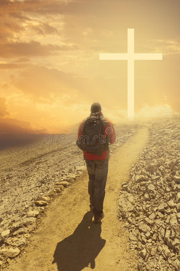 Man walking to the cross. Man on top of the mountain looks to a cross of light. Bright atmosphere stock photo