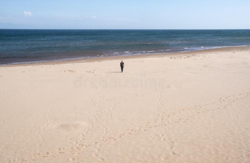 Man Walking Towards the Ocean on Deserted Brackley Beach in PEI royalty free stock photography