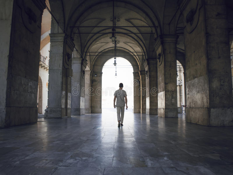 Man walking under heavy vaults, in Pisa, Italy. Bright light seeping in. Man walking under heavy stone vaults, in Pisa, Italy. Bright light seeping in over the stock photography