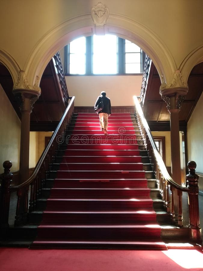 man walking up stairs in colonial style building stock images