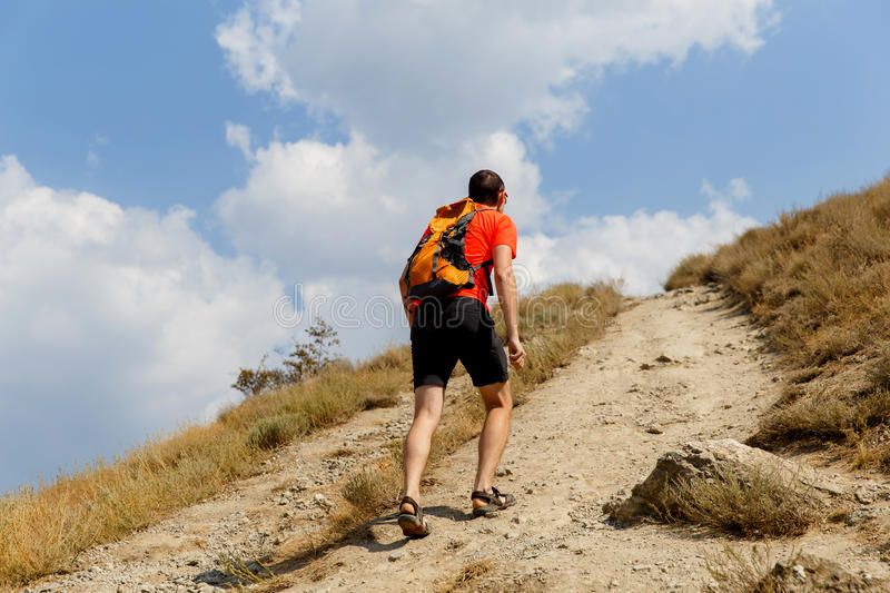 Man walking up steep mountain. Summer day royalty free stock photography