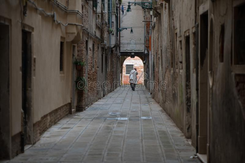 A man walking a a Venetian street. Streets of Venice, Italy royalty free stock images