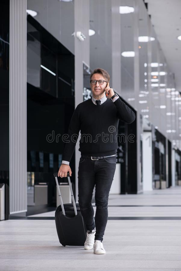 Man walking with wheeled bag. At airport terminal and talking on phone royalty free stock images