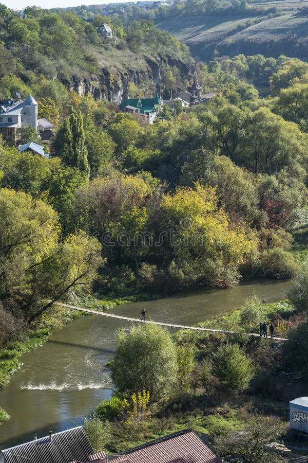 Man walks across a bridge over the Smotrych River in the canyon of Kamianets-Podilskyi stock photography