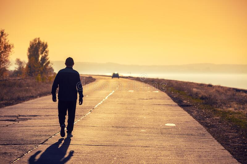 A man walks along a concrete road at sunset royalty free stock photos