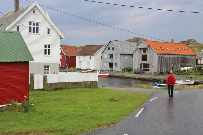 A man walks along a street on the tiny Island Utsira, Norway. Some houses close to the northern port. Utsira lies in the North Sea, about 18 kilometers West of stock photos