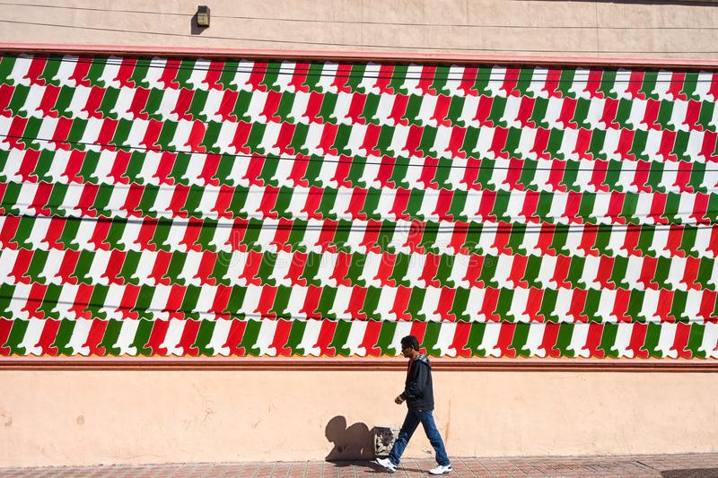 Man walks by a colourful wall in Saltillo Mexico. January 17, 2016 Saltillo, Mexico: a man walks by a large mosaic of national colours in the historic downtown stock images