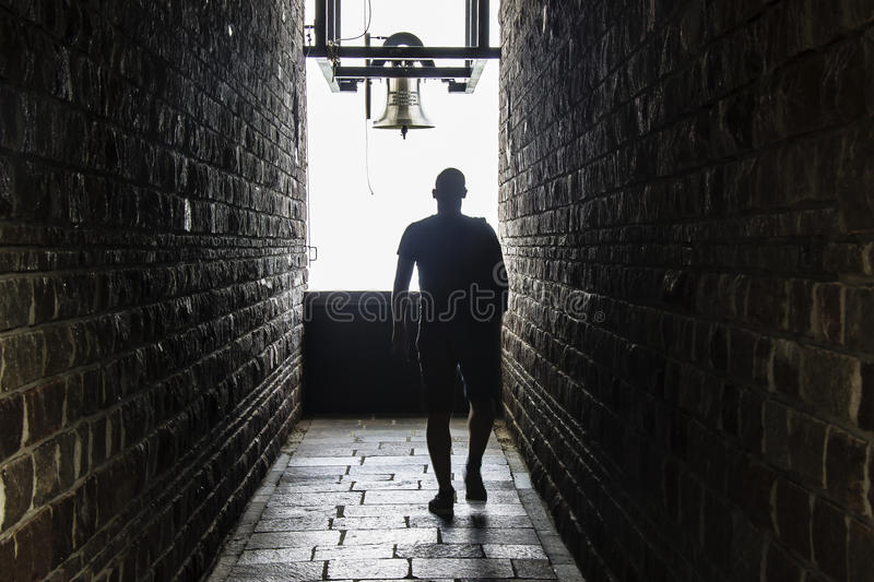A men walks into a dark tunnel, but a light shows at the end stock photography