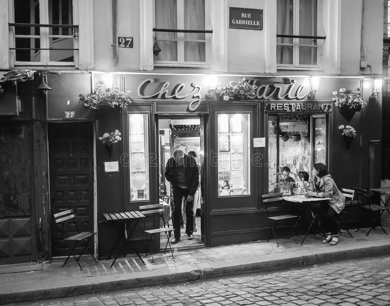 Man walks out door of Chez Marie Restaurant on Montmartre, Paris. Black and white photo. Man walks out door of Chez Marie Restaurant on Montmartre. More diners stock image