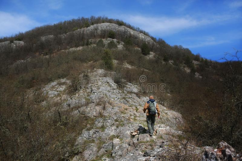 Man walks on a rocky hillside. Redhead man in a brown-and-blue windbreaker with backpack walks on a rocky hillside in the spring Crimean forest. There are no stock photography