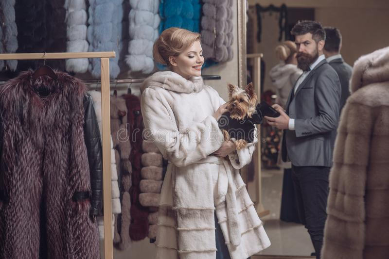 Man with wallet and girl among furry coats royalty free stock photo