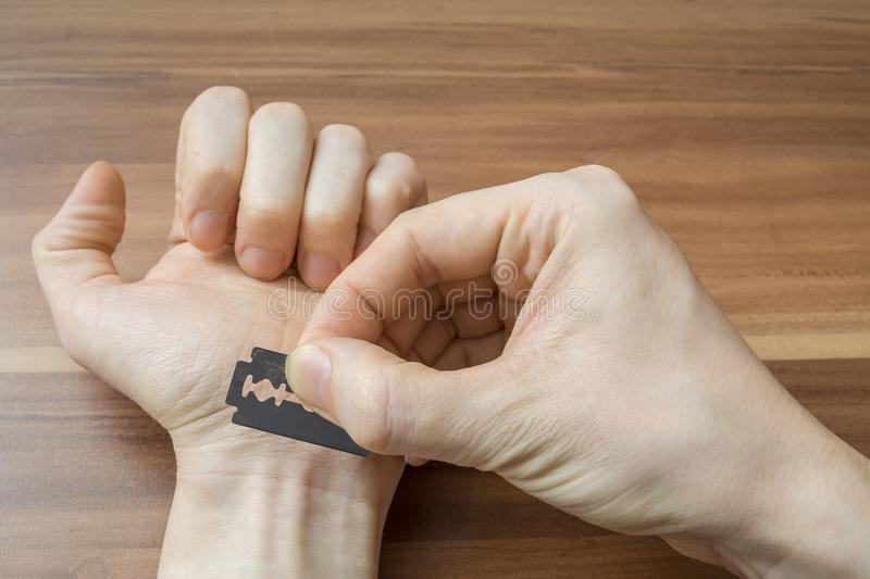 Man wants to cut vein on hand with razor. Suicide concept royalty free stock photo