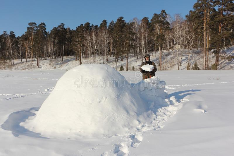 Man in warm clothes building an igloo on a snowy glade in the winter, Siberia, Russia royalty free stock photography