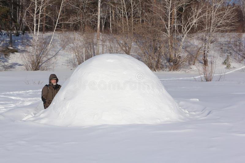 Man in warm clothes sitting by an igloo on a glade in the winter, Siberia, Russia royalty free stock photo