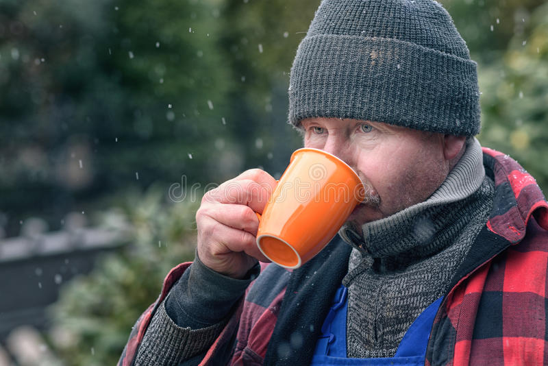 Man in a warm jacket and beanie drinking coffee. Man in a knitted wool beanie, jersey and jacket standing outdoors in the snowy winter weather drinking hot royalty free stock photos