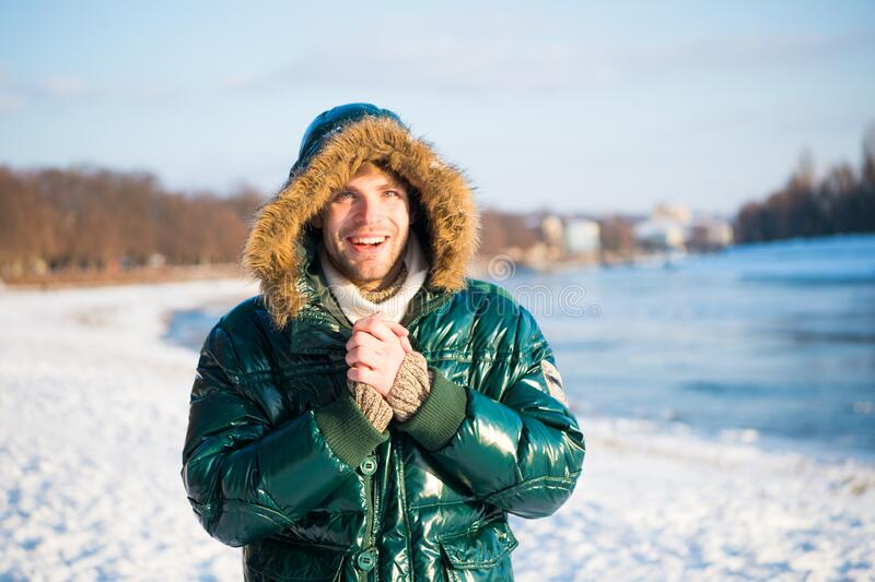 Man warm jacket snowy nature background. Wind resistant clothes. Winter favorable weather conditions. Sunny winter day stock photos