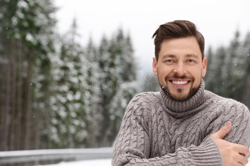 Man in warm sweater outdoors on snowy day, space for text. Winter. Vacation stock photos