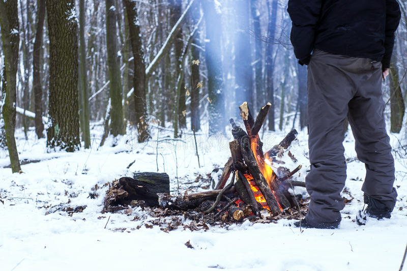 Man warming his hands around a campfire in the forest. Snow royalty free stock photos