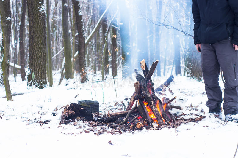 Man warming his hands around a campfire in the forest. Snow royalty free stock image