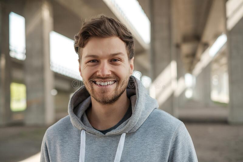 Cheerful sportsman in a hoodie outdoors royalty free stock photography