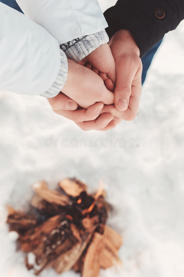 Man warms hands of a woman in his hands over snow and firewood background. The concept of lover at winter camping, hiking, recreation, tourism or destitute royalty free stock photography