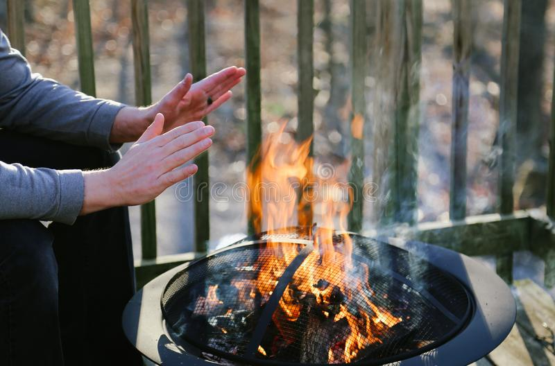 Man Warms His Hands Over a Fire Pit on a Deck. stock photography